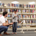 Hugo with a child at the Library