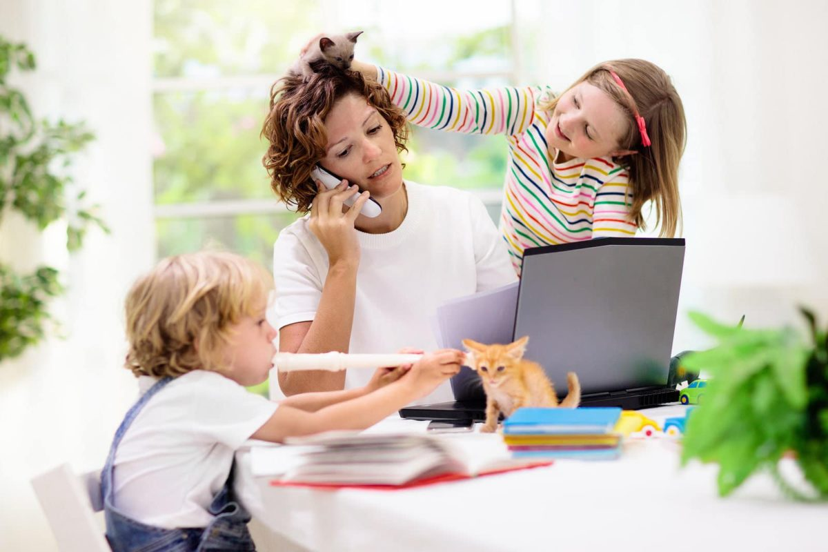 Mother working from home with children