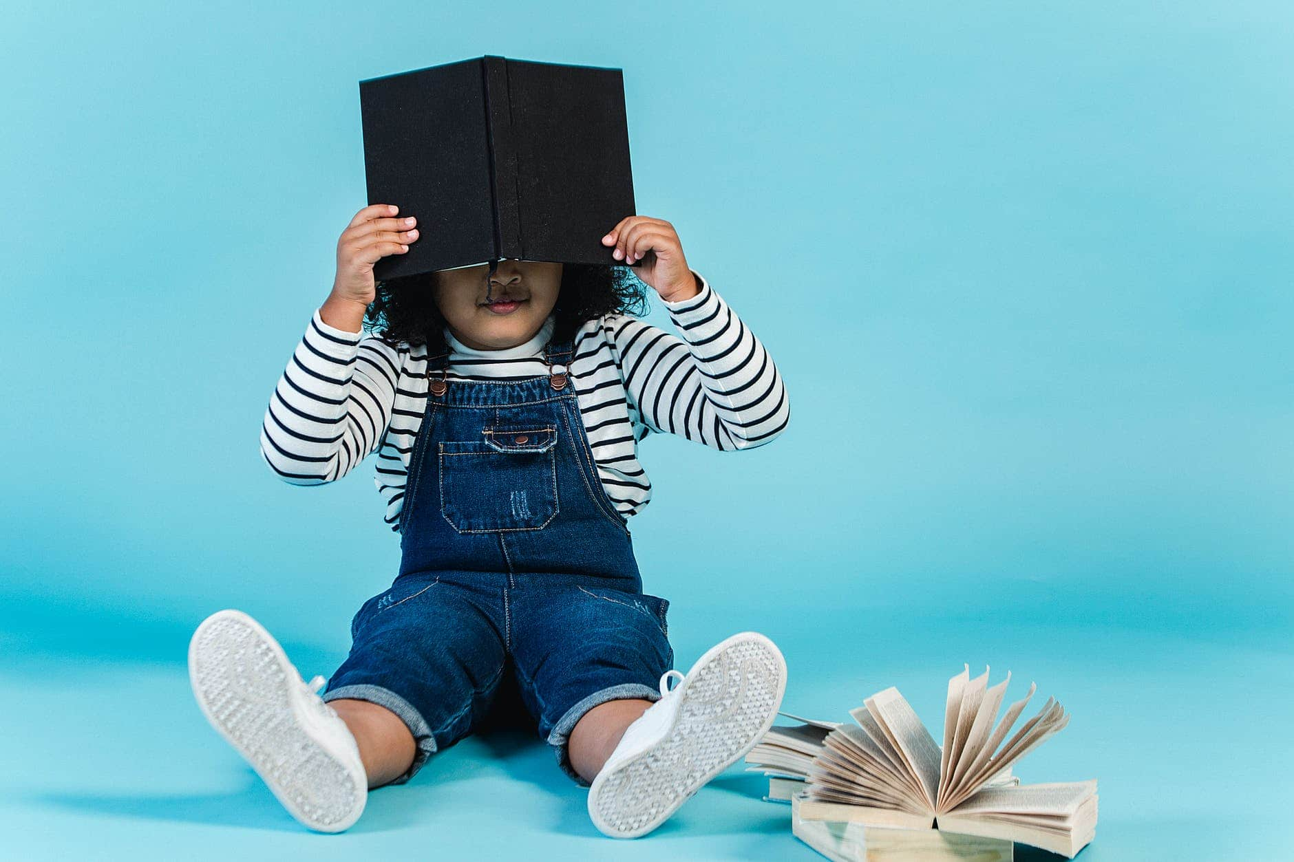 small black girl sitting on floor with books in studio